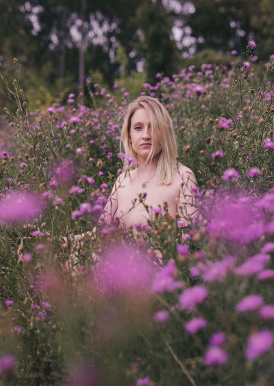Beautiful young woman standing by purple flowering plants on field