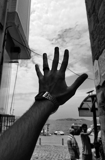 Cropped hand gesturing against sky