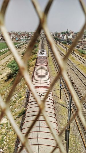 Railroad track seen through chainlink fence