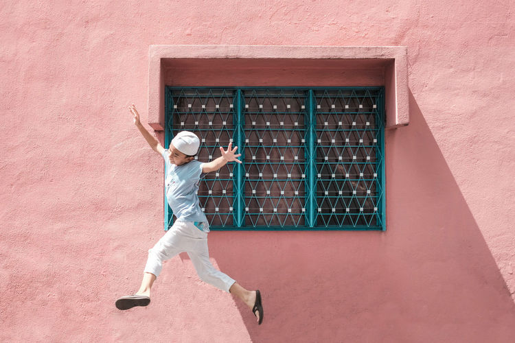 Full length of smiling boy jumping standing against wall