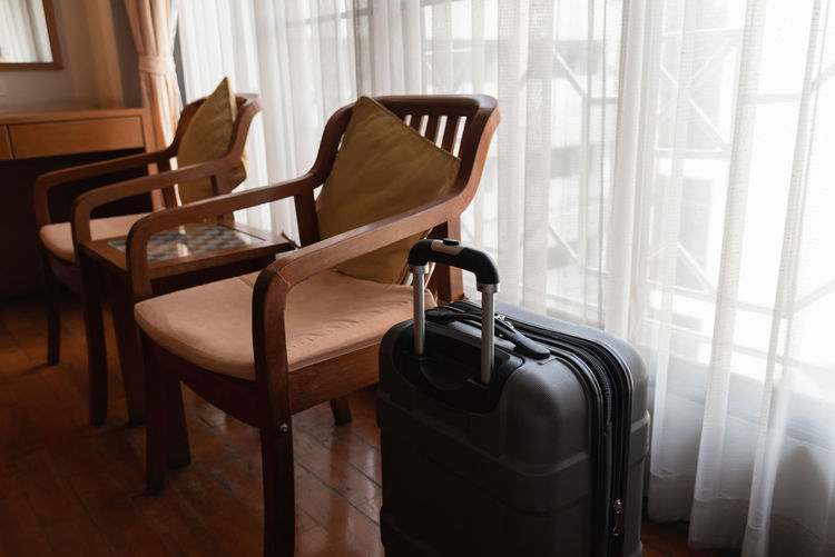 Luggage by empty chairs at home