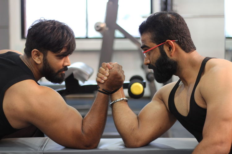 Male Friends Arm Wrestling At Gym