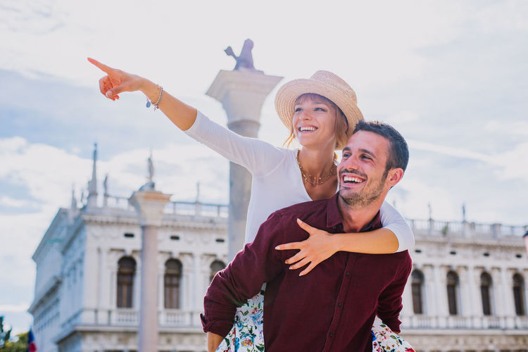 Happy man piggybacking girlfriend while standing in city