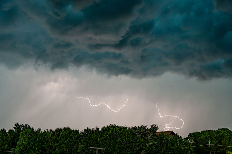 Low angle view of lightning in sky at dusk