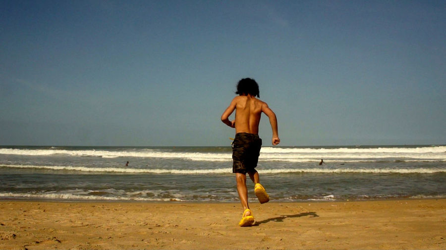 Rear view of shirtless boy running towards sea at beach against clear sky