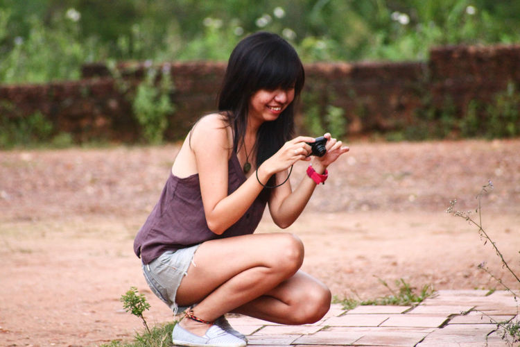 Teenage girl using mobile phone while sitting outdoors