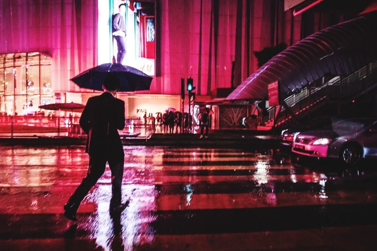 real people, full length, night, illuminated, wet, water, one person, standing, architecture, men, women, building exterior, outdoors, under, city, people