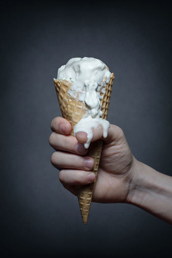 Cropped hand holding ice cream cone against gray background
