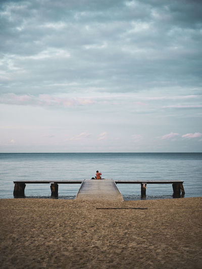 Woman sitting on pier over sea against sky