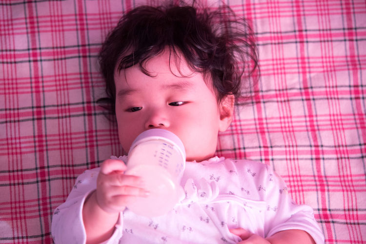 Close-Up Of Cute Baby Holding Milk Bottle While Lying On Blanket