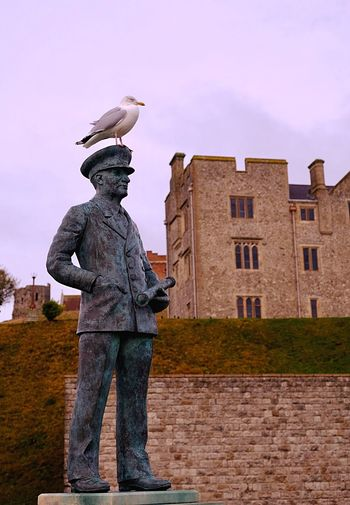 Low angle view of bird perching on statue against sky