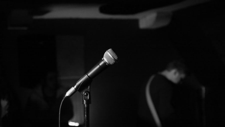 Close-up of microphone against musician standing in recording studio