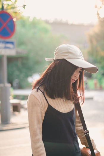Rear view of woman wearing hat against blurred background