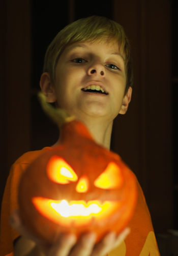 Portrait of smiling boy with pumpkin at home