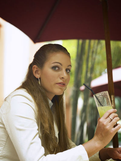 Portrait Of Businesswoman Having Drink At Cafe