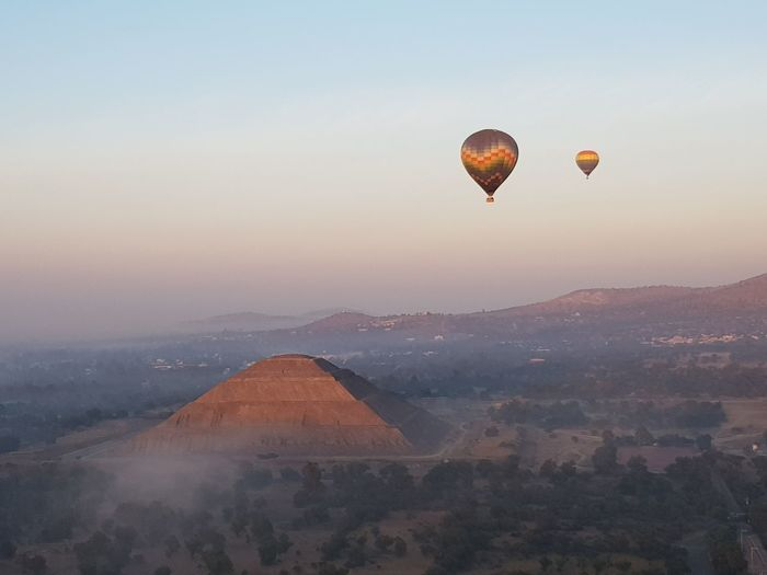 Hot air balloons flying over ancient pyramid in mist against sky during sunrise