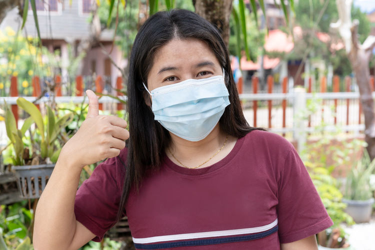 Adult woman wearing medical face mask. pretty middle female showing finger thumb up for good sign.