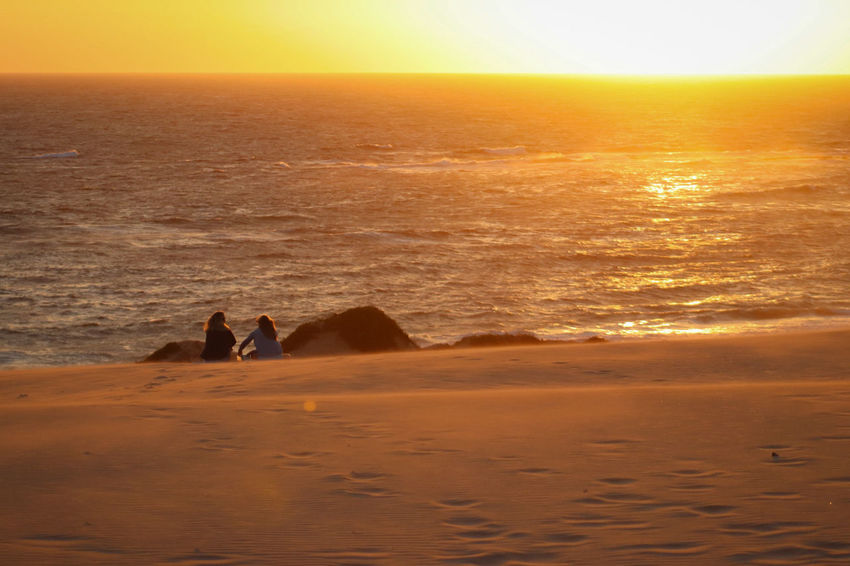Friends and sunsets. Sunset Travel Destinations Sea Sand Vacations Sunlight Silhouette Beach Scenics Nature Outdoors Beauty In Nature No People Horizon Over Water Day Sky People Orangesky