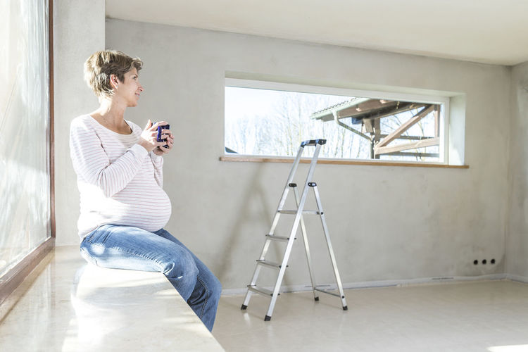 Pregnant woman holding cup while sitting by window at home