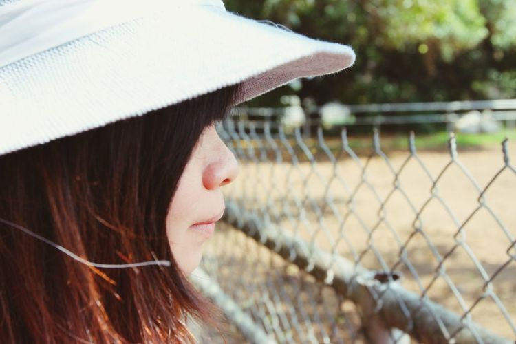 Close-up of young woman standing by chainlink fence at park