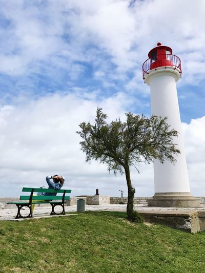 Man Sitting On Bench Against Lighthouse