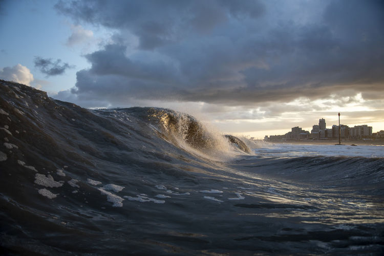 Sea waves splashing against cloudy sky during sunset