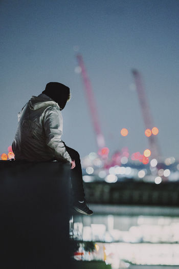 Man sitting on riverbank against sky at night
