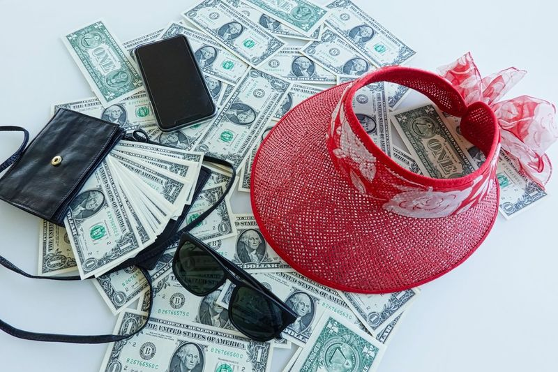 Sunglasses Sunhat Travel Destinations Cellphone Money Dollar Still Life Indoors  No People Close-up Currency Paper Currency Glasses Wealth Finance High Angle View Studio Shot Fashion Red Text Creativity Art And Craft Eyeglasses  Sunglasses Multi Colored White Background