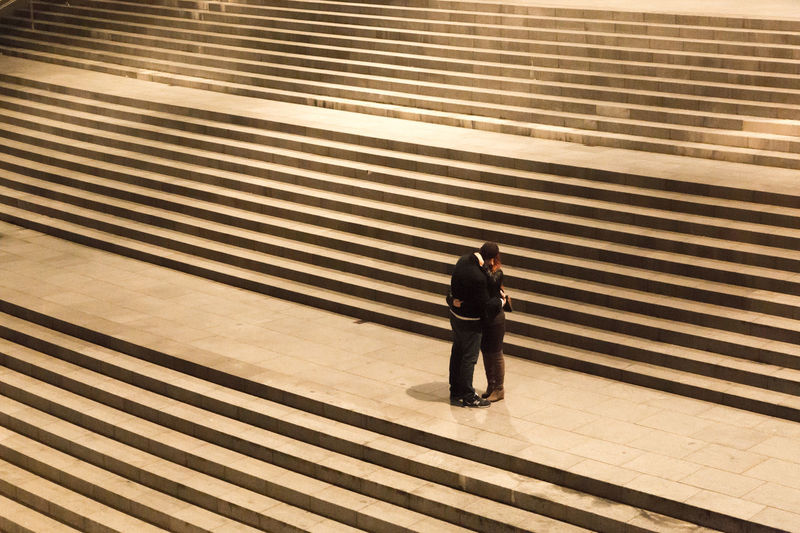 Couple kissing while standing on steps