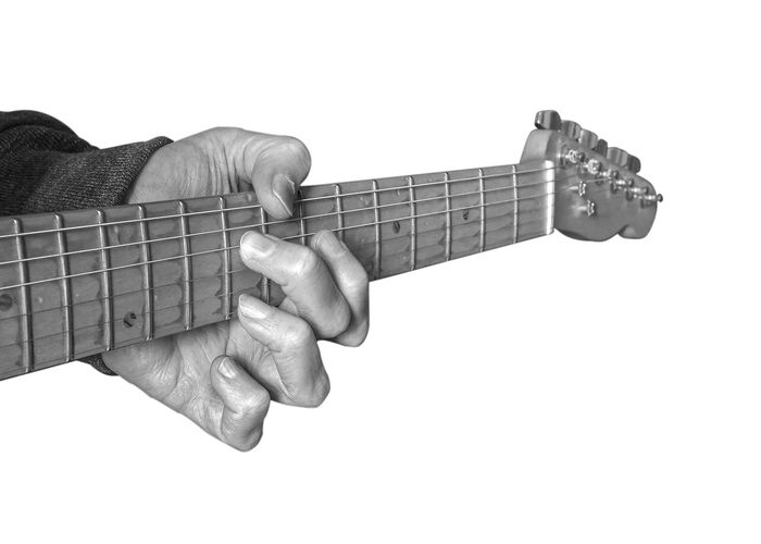 Close-up of hand playing guitar against white background