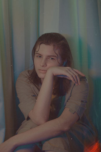 Portrait of a girl sitting against wall