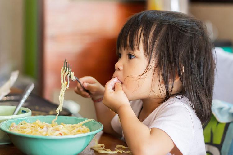 Cute baby girl eating noodles