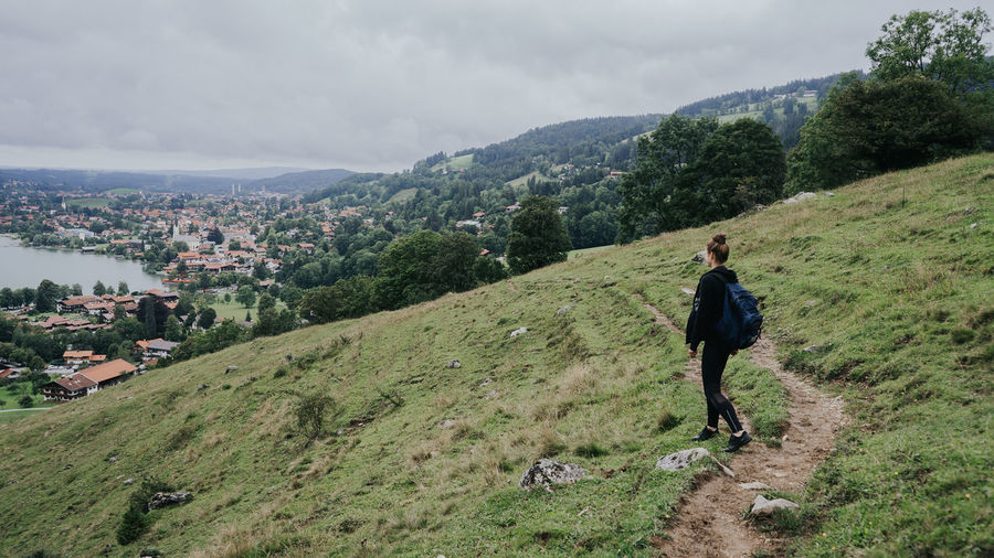 Full length of woman walking on mountain road hiking in germany schliersee