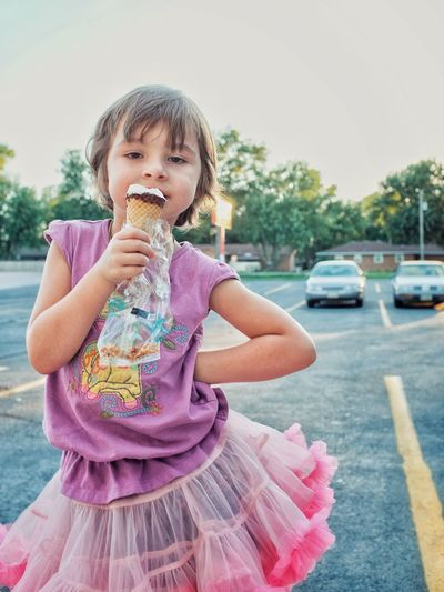 Portrait of girl eating ice cream on street