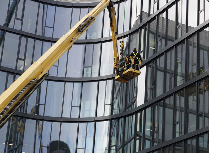 workers on a crane Built Structure Architecture Low Angle View Building Exterior Working Occupation Building Glass - Material Day Men People RISK Real People Outdoors Modern Cleaning Office Building Exterior Modern Architecture Man At Work Men At Work  Crane Construction Worker