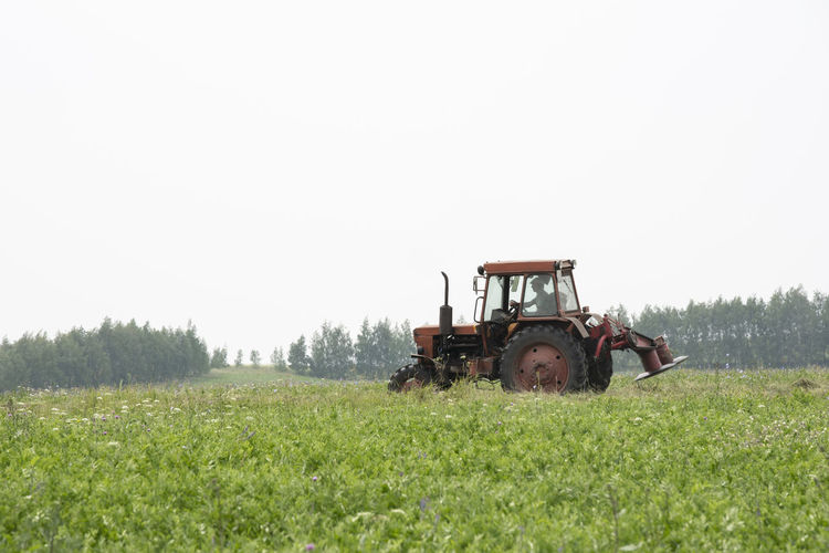 Man driving tractor on field against clear sky