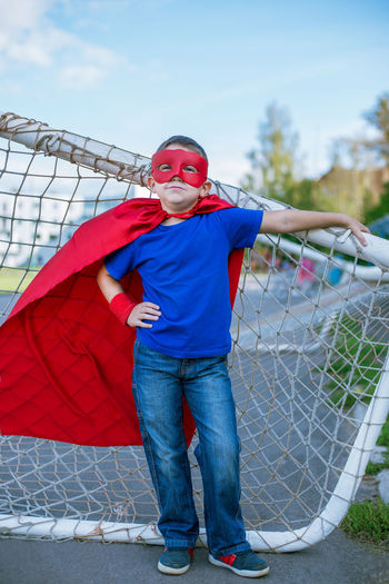 Full length portrait of boy wearing cape while standing by net