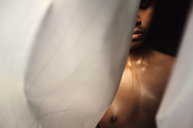 Close-Up Of Shirtless Man Seen Through Curtain