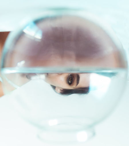 Close-up portrait of boy in glass