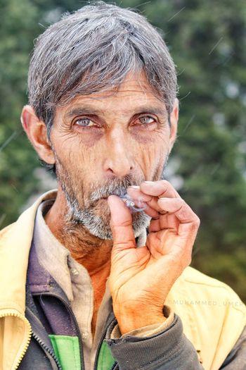 Close-up portrait of senior man smoking beedi