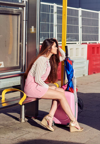 Woman sitting at bus stop in city