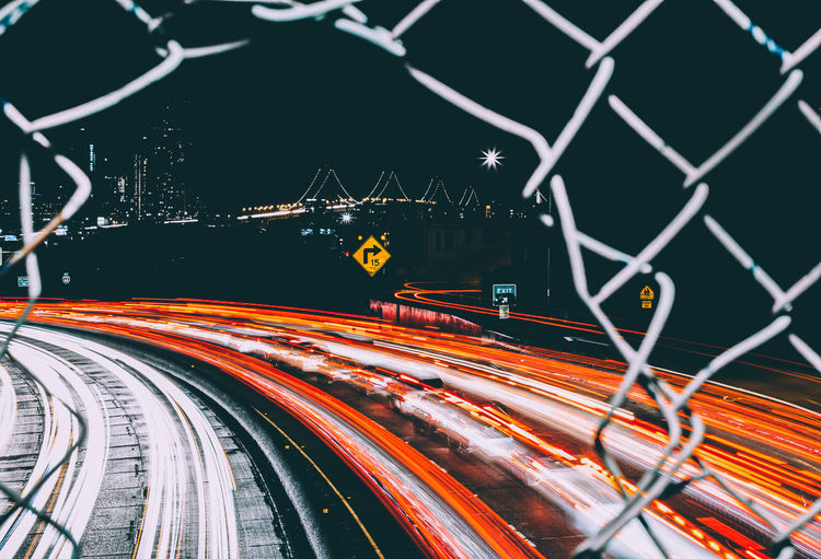 Light trails on road seen through chainlink fence
