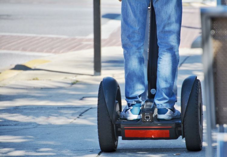 Low Section Of Man Riding On Segway At Sidewalk