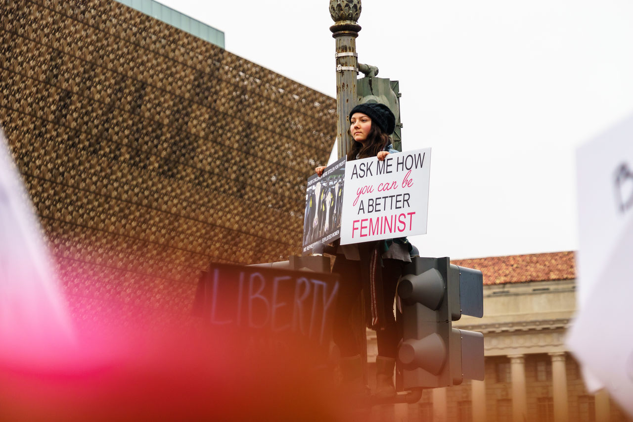 Low angle view of woman holding placard with message while standing in city against sky