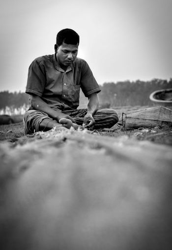 Surface Level Of Man Sitting On Field Against Sky