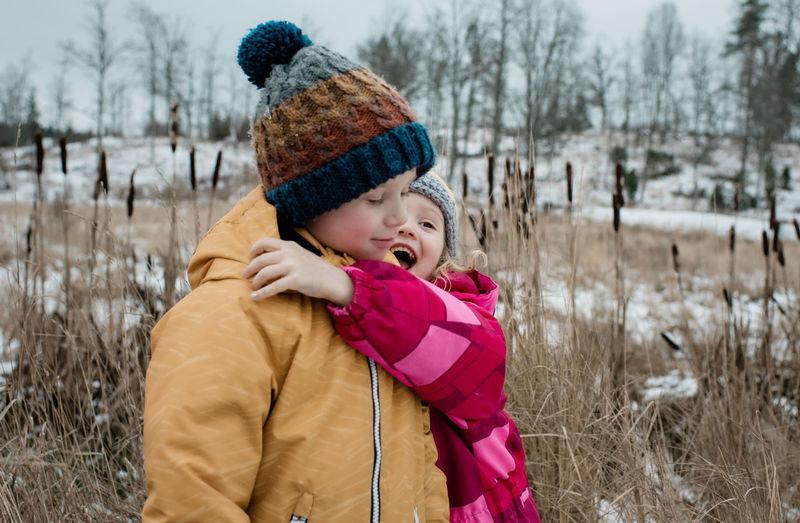Boy wearing hat on field during winter