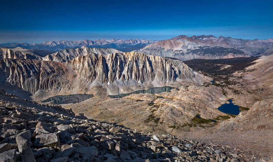 What was laid out before my eyes | On our way down from Mt. Whitney summit, till we reached back Trail Crest, I couldn't help myself making frequent stops and gazing at what was laid out before my eyes. Yes, I had been here before. It wasn't the first time. But, how would I know whether or not there would be another time? I was just getting most out of that moment, which would never return. Right in front of me, Mt. Hitchcock towered over the beautiful Hitchcock Lakes. And there was the equally amazing Guitar Lake to the right. We spent the last two nights at both lakes! If you look farther out, beyond the Kern River Canyon, Mt. Kaweah, Second Kaweah, Red Kaweah and Black Kaweah made up their own mountain skyscraper! We started our 73-mile excursion from Crescent Meadow way behind it. In fact, the Great Western Divide, which we had crawled over via Kaweah Gap several days ago, continued to stretch far to the left of the frame. It marks the Sequoia National Park boundary. It is truly mind boggling to look back at the mountain range where we backpacked for the last 8 days in a different perspective. Inyo National Forest, CA Above Timberline Adventure Backcountry Beauty In Nature Great Western Divide Guitar Lake High Sierra High Sierra Trail Hitchcock Lakes Inyo National Forest John Muir Trail Kern River Canyon Landscape Landscape Photography Mountain Mountain Peak Mountain Range Mt. Hitchcock Mt. Whitney Nature No People Sequoia National Park Sierra Nevada Sky Wilderness