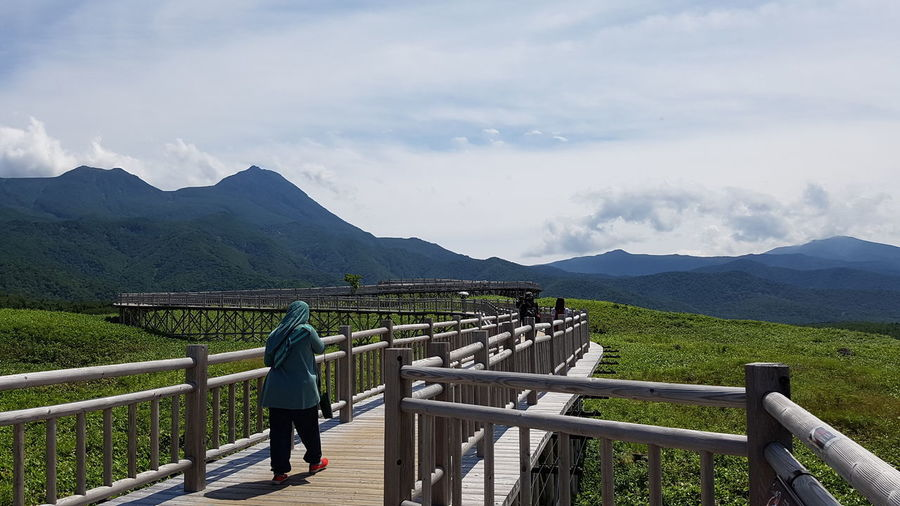 Rear view of mid adult woman walking on footbridge against cloudy sky during sunny day