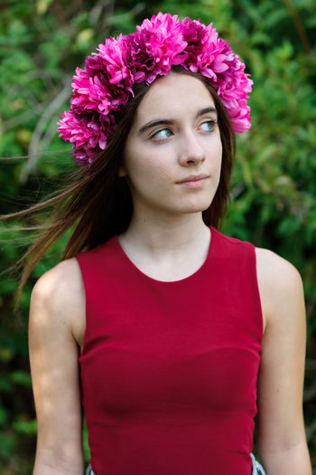 Portrait of beautiful young woman standing against red flowering plant