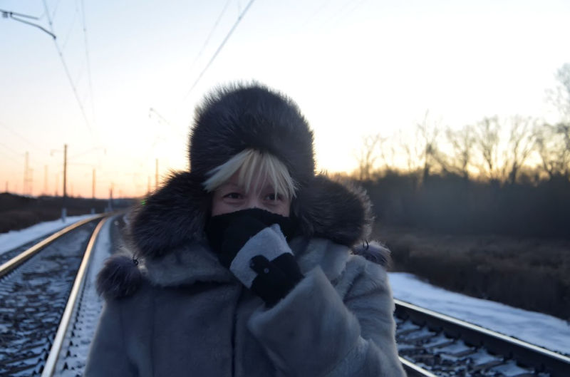 Woman Wearing Warm Clothing And Fur Hat Standing On Railroad Against Sky During Sunset